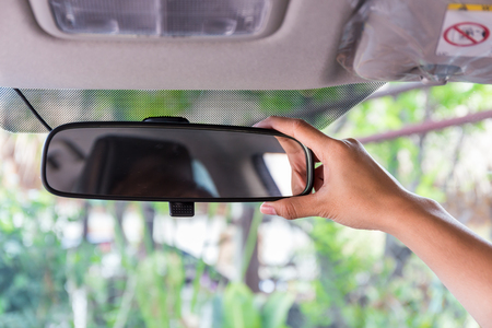 Women hand adjusting rear view mirror.