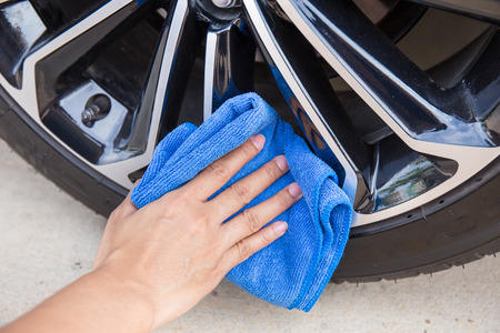 microfiber cloth: Hand with blue microfiber cloth cleaning car wheel.