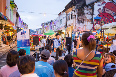 play popular: PHUKET, THAILAND MAY 29, 2016: Musician play saxophone jazz at night market of Phuket on May 29, 2016.among old building Chino Portuguese style, street of Phuket town is the famous popular