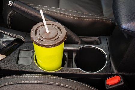 water feature: Coffee or tea mugs green placed on the vehicle console in modern luxury car interior