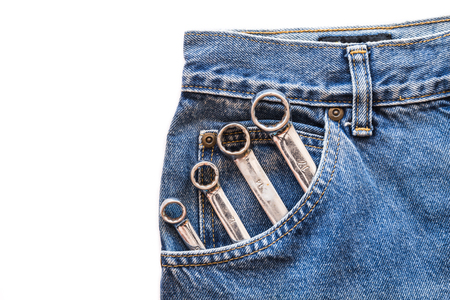 lug: chrome lug  spanner in front blue jeans pocket on white isolated background. Copy space for text