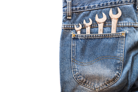 lug: chrome lug wrench in back blue jeans pocket on white isolated background. Copy space for text Stock Photo