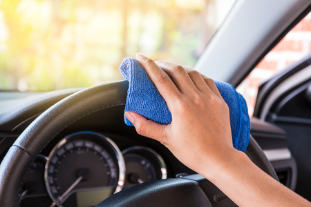 rag wheel: Hand with microfiber cloth cleaning Interior and steering wheel modern car. Stock Photo