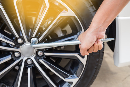 pneumatic tyres: Hands disassembling a modern car wheel (steel rim) with a lug wrench for change wheel