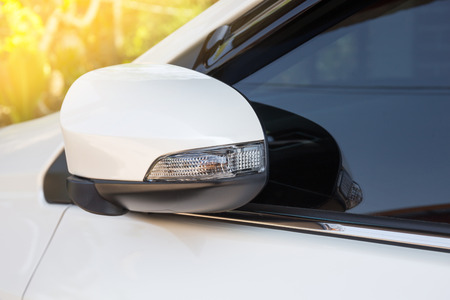 automobile door: modern white car side view mirror folded with turn signal