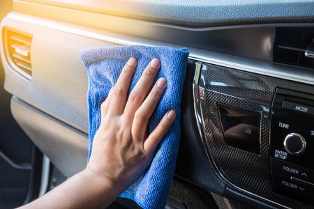rag wheel: Hand with microfiber cloth cleaning Interior modern car.