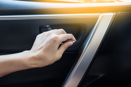 unlocking: Woman driver pressing button locking and unlocking doors in car.