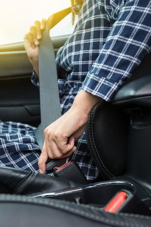 cinturon de seguridad: Primer de la mano de la mujer la fijación de un cinturón de seguridad en el coche
