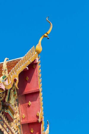 closeup detail of ornately decorated temple roof in bangkok, thailand on blue sky Stock Photo