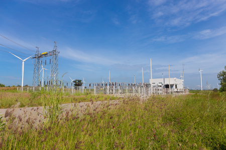 electricity pylons and power plant or station with wind turbine in nature outdoor Stock Photo