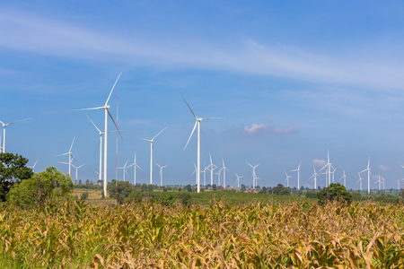 Eco power, Wind turbine on the green grass and corn field over the blue cloudy sky Stock Photo