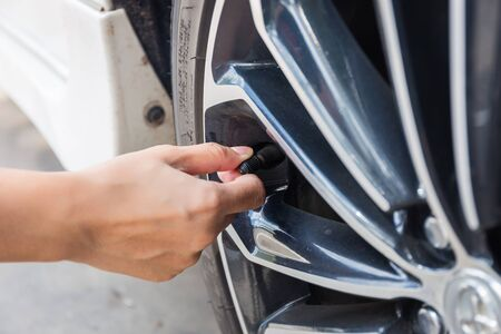 air pressure: Man checking air pressure and filling air in the tires of car. Concept picture