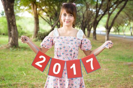 hand holding paper: smile of cute woman hand holding paper sign 2017, happy new year