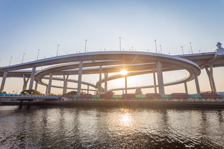 Modern concrete bridges the ways across big river in sunset time with sunlight. Stock Photo