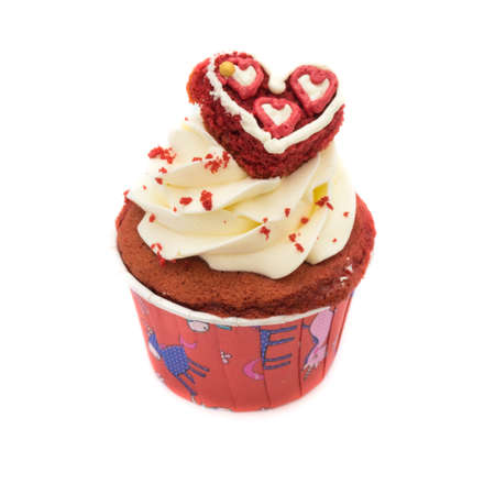 Chocolate cupcake decorated with red heart icing and sprinkles isolated on white 免版税图像