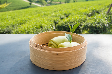 Steamed bun and green tea leaves in battered bamboo on table with tea plantation background at Choui Fong Chiang Rai province, Thailand.