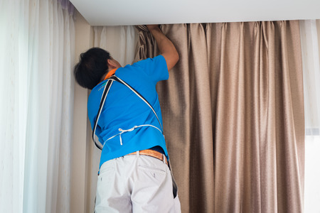 Handy man home Installation and repair service technician or home owner hanging curtains for the window treatment in a new house. Foto de archivo