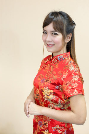 Asian woman greeting in traditional chinese or cheongsam with asian woman greeting in traditional chinese or cheongsam with hand lift welcome expression and lucky in m4hsunfo