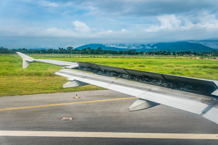 The wing of the aircraft with flaps open when landing for stop on a weather bad day. 版權商用圖片