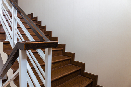 Staircase custom built home interior with wood staircase and white walls. Copy space background