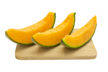 Closeup melon bright colors that is pieces on wooden tray isolated on white background.