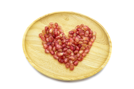 Fresh pomegranate heart shape on wooden plate isolated on white background