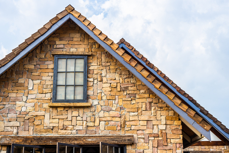 Classic roof decorated with stone and wood in vintage style. Traditional building