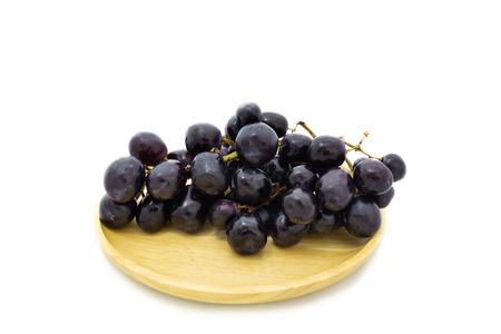 Fresh grapes on wooden plate isolated on white background Reklamní fotografie