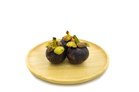 Fresh mangosteen on wooden plate isolated on white background
