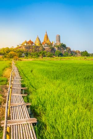 Krajobraz świątyni Wat Tham Sua (Świątynia Jaskinia Tygrysa) z polami ryżu jaśminowego w prowincji Kanchanaburi, Tajlandia. Jest ważnym punktem orientacyjnym, który każdy musi odwiedzić
