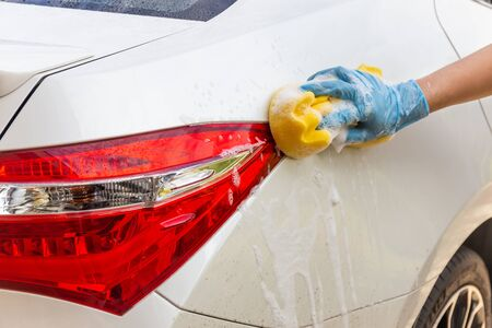 Woman hand wearing blue gloves with yellow sponge washing taillight modern car or cleaning automobile. Car wash concept