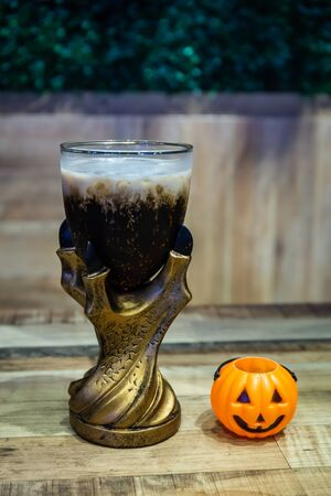Black cola drink in a magic fantasy glass with a pumpkin, Halloween symbol on the table in Halloween night party Banque d'images - 131904637