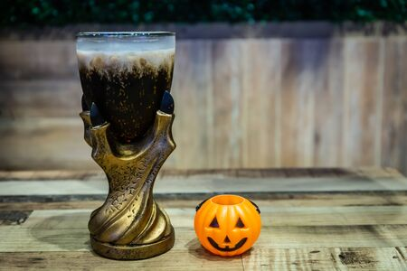 Black cola drink in a magic fantasy glass with a pumpkin, Halloween symbol on the table in Halloween night party Banque d'images - 131904707