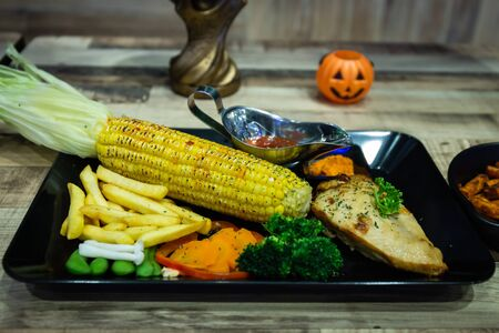 Chicken steak with corn and potatoes on a black plate and cola drinks, pumpkin at the Halloween party. Stock Photo