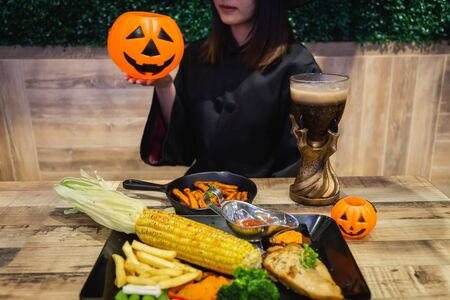 Beautiful young surprised woman or Halloween Witch dark style with holding a pumpkin and black drink, food in Halloween celebrate night party. Copy space background and soft or select focus