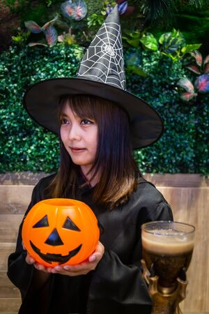Beautiful young surprised woman or Halloween Witch dark style with holding a pumpkin and black drink in Halloween celebrate night party. Copy space background and soft or select focus