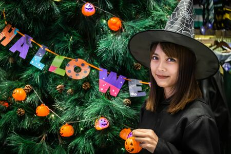Beautiful young surprised woman or Halloween Witch dark style with holding a pumpkin in Halloween celebrate night party. Copy space background and soft or select focus