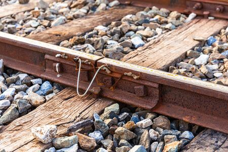 Close up of old connecting point train or railroad tracks with wooden backing In the countryside Thailand