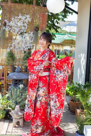 The girl is wearing a red traditional kimono, which is the national dress of Japan