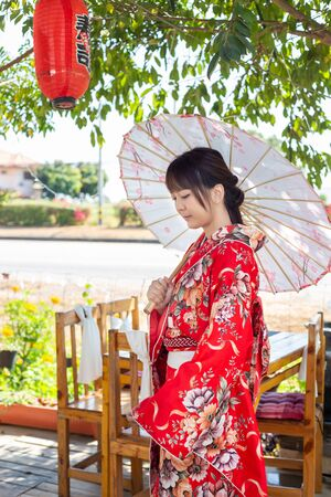 The girl is wearing a red traditional kimono, which is the national dress of Japan and Hold an umbrella
