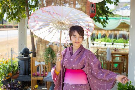 The girl is wearing a pink traditional yukata, which is the national dress of Japan and Hold an umbrella Stok Fotoğraf