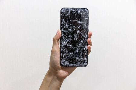 Woman hands holding smartphone with broken or cracked screen on white background. Not available to use, shop online and do business concept. Select focus
