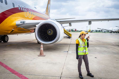 BANGKOK THAILAND - MAY 29, 2016: A female staff at Don Mueang Airport is coordinating a check before the plane takes off.
