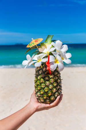 Tropical exotic pineapple cocktail with plumeria on hand at the beach with white sandy and blue sea 版權商用圖片