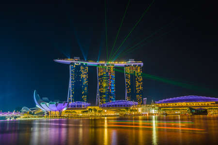 Singapore - November 20 2016: Modern architecture Singapore skyline at dusk with reflection and light color show in night time. Singapore is an island city-state in Southeast Asia.