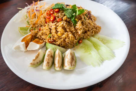 Fried rice with tom yum chili paste with eggplant, cucumber and salted egg.Thai food