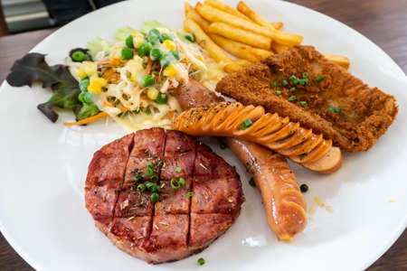 Beef steak, hot dog, fried chicken with whole grain salad and potatoes