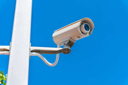 Digital surveillance camera is mounted on a pole with the blue sky in the background.