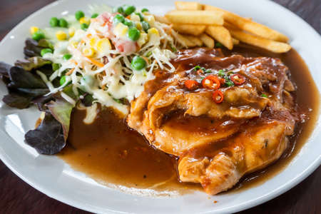 Chicken steak in a sauce with lettuce and potatoes in a white plate on the table.