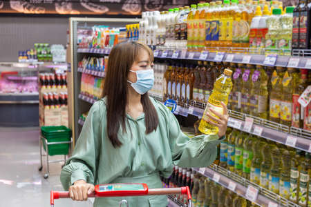 Women wear masks to shop cooking oil in supermarkets Banque d'images